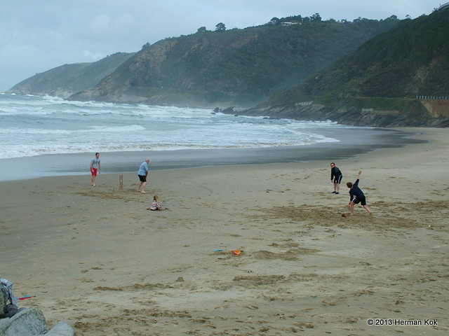 Family playing cricket on the beach