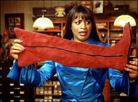 Lola from Kinky Boots holding a burgandy boot