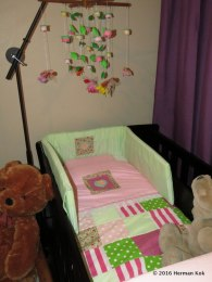 Cot with mobile above it